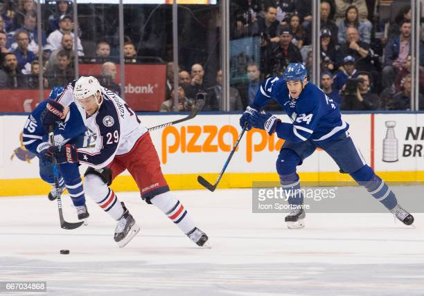 Columbus Blue Jackets left wing Lauri Korpikoski skates with the puck as Toronto Maple Leafs center Brian Boyle gives chase during the first period...