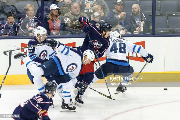 Columbus Blue Jackets left wing Sonny Milano and Winnipeg Jets left wing Brendan Lemieux battle for a loose puck during the first period in a game...