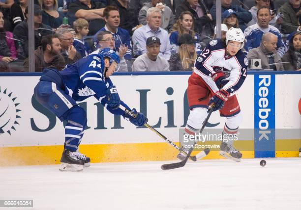 Columbus Blue Jackets left wing Sonny Milano battles with Toronto Maple Leafs defenseman Morgan Rielly during the third period in a game on April 9...