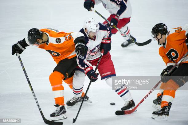Columbus Blue Jackets Right Wing Oliver Bjorkstrand keeps the puck from Philadelphia Flyers Center Valtteri Filppula and Philadelphia Flyers Winger...
