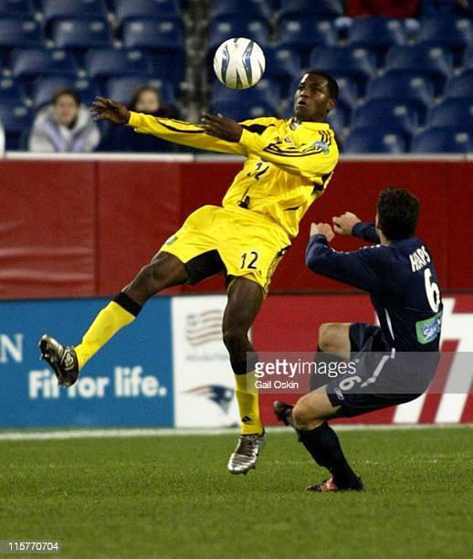 Columbus Crew Edson Buddle left heads the ball as New England Revolution Jay Heaps right falls to the ground at Gillette Stadium in Foxborough...
