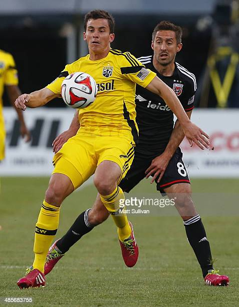 Columbus Crew midfielder Bernardo Anor fights for the ball with DC United midfielder Davy Arnaud during the first half of their game at Columbus Crew...