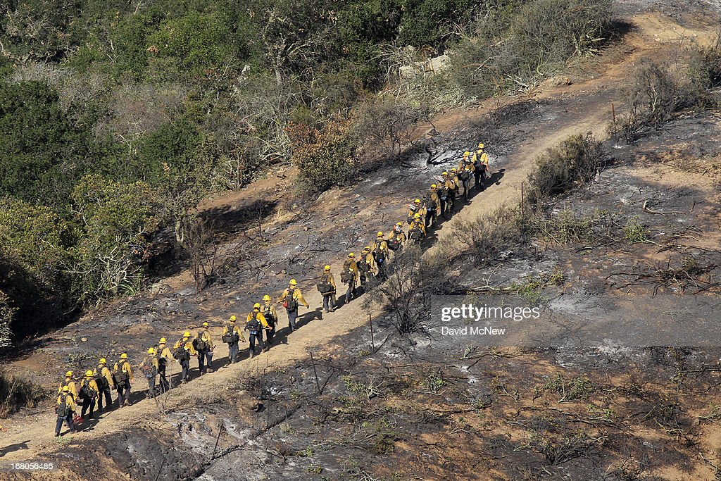 A column of elite U.S. Forest Service Hotshot firefighters walk along the edge of the black near Hidden Valley at the Springs fire on May 4, 2013 near Camarillo, California. Improving weather conditions are helping firefighters get the upper hand on the wildfire which has grown to 28,000 acres and is now 56 percent contained.