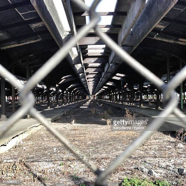 Columns supporting overpass viewed through chainlink fence