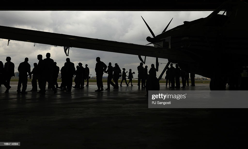 People gather inside a hanger at Centennial Airport for the annual Colorado wildfire briefing and press conference with Colorado Governor John Hickenlooper, May 09, 2013. Inside the hanger is an aircraft, that is stationed in Colorado, used to drop slurry during the initial attack of a wildfire.