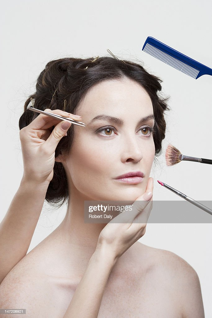 Comb, tweezers and makeup brushes surrounding woman's face : Stock Photo