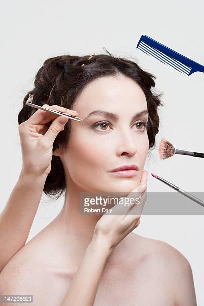 Kamm, Pinzette und Make-up-Pinsel umliegenden woman's face