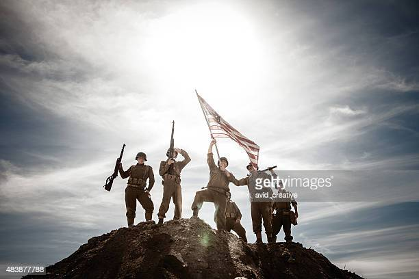 WWII Combat Infantry Squad Waves Flag on Hill