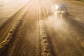 A combine harvester is harvesting grain crops on a cornfield in the evening sun seen from above