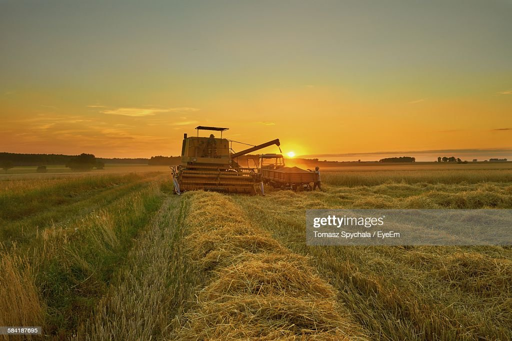Combine Harvester Tractor On Field Against Sky During Sunset