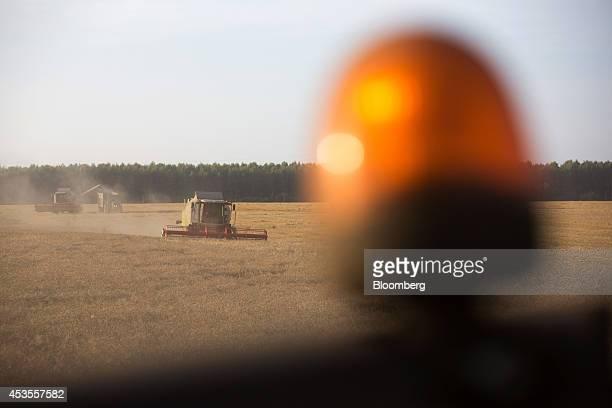Combine harvesters drive across a wheat field during the summer harvest on the OOO Barmino farm enterprise in Vargany near Nizhny Novgorod Russia on...