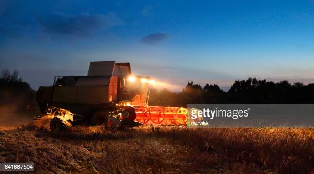 Combine harvesting barley by night