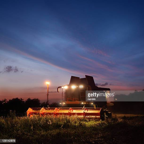Combine working on the field by night