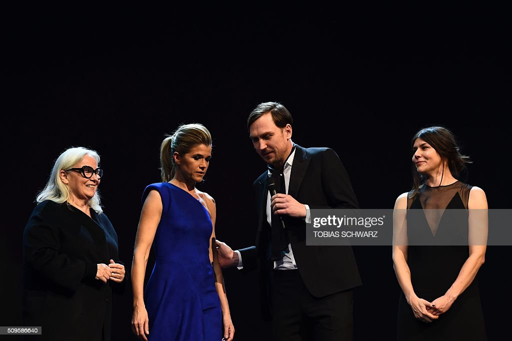 TV host Anke Engelke speaks with French photographer and jury member Brigitte Lacombe, German actor and jury member Lars Eidinger and Polish film maker and jury member Ma?gorzata Szumowska on stage prior to the film 'Hail, Caesar!' screening as opening film of the 66th Berlinale Film Festival in Berlin on February 11, 2016. Eighteen pictures will vie for the Golden Bear top prize at the event which runs from February 11 to 21, 2016. / AFP / TOBIAS SCHWARZ