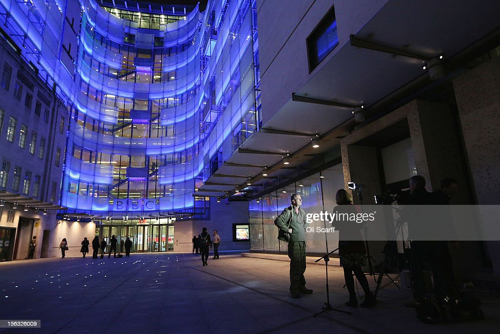 Comedian Arthur Smith (4th R) is interviewed outside the BBC headquarters at New Broadcasting House which is illuminated at night on November 13, 2012 in London, England. Tim Davie has been appointed the acting Director General of the BBC following the resignation of George Entwistle after the broadcasting of an episode of the current affairs programme 'Newsnight' on child abuse allegations which contained errors.