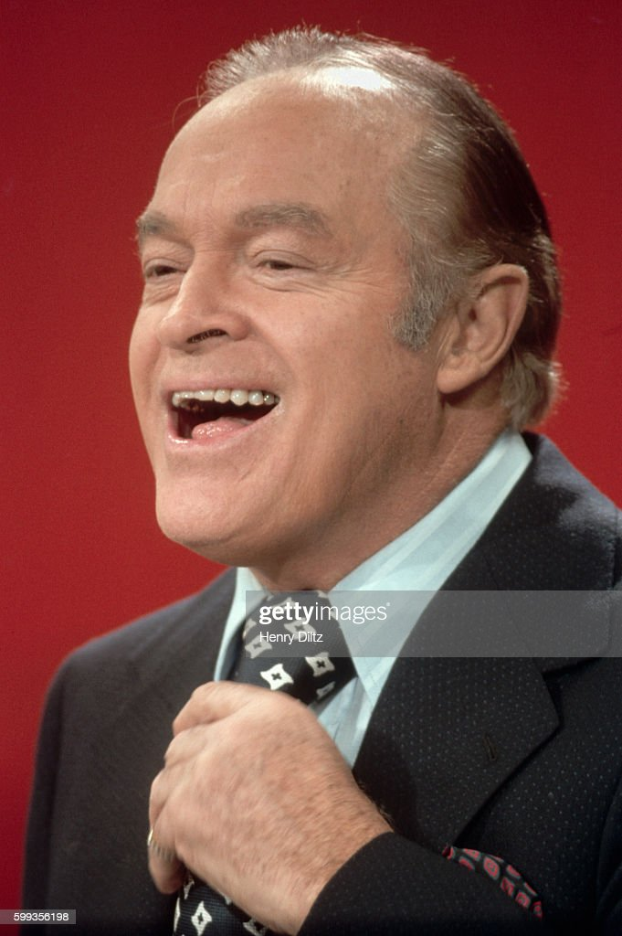 Comedian Bob Hope adjusts his tie and laughs during the filming of one of his many television specials.