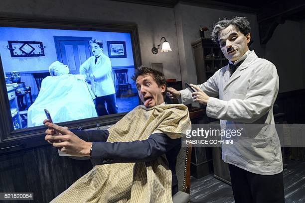 Comedian Gus poses for a selfie next to a wax statue of Charlie Chaplin during a press visit of Chaplin's World Museum in CorsiersurVevey western...