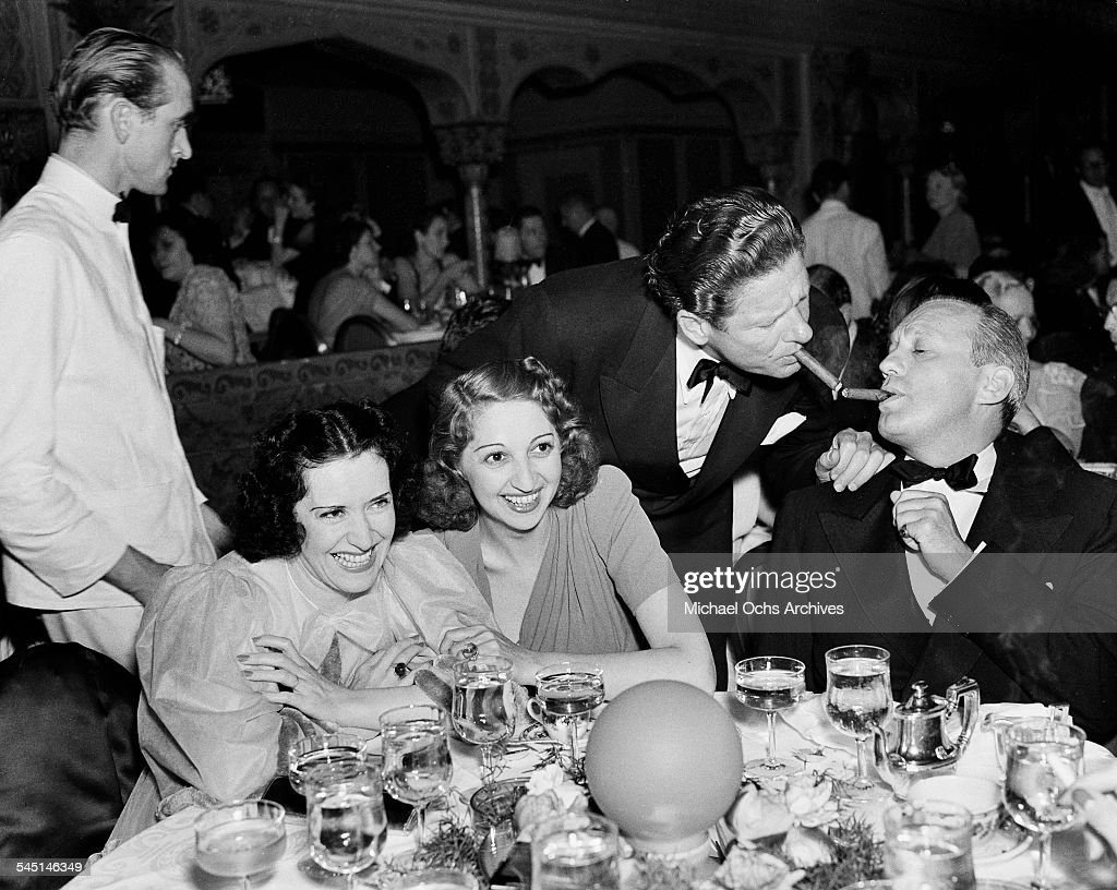 Comedian Jack Benny has his cigar lit as his wife Mary Livingston and friend Gracie Allen share a laugh during an event in Los Angeles California