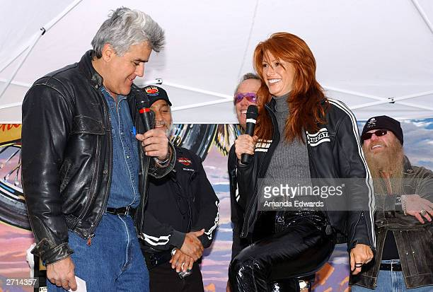 Comedian Jay Leno teases actress Angie Everhart about her patent leather pants at the Love Ride 20 at HarleyDavidson/Buell of Glendale November 9...