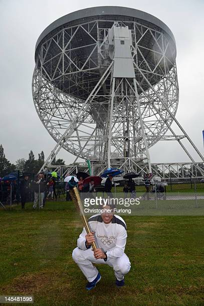 Comedian John Bishop carries the Olympic Torch to the dish of The Lovell Telescope at Jodrell Bank on May 31 2012 in Holmes Chapel England The...