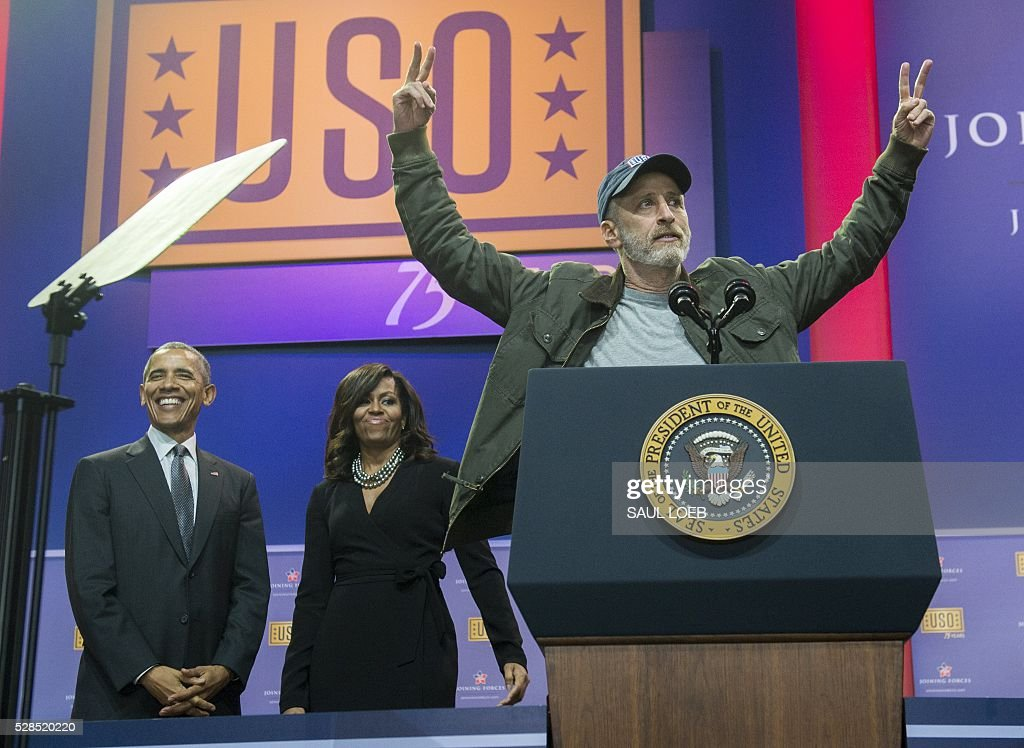 Comedian Jon Stewart speaks alongside US President Barack Obama and First Lady Michelle Obama during a celebration of the 5th anniversary of Joining Forces and the 75th anniversary of the USO at Andrews Air Force Base in Maryland, May 5, 2016. / AFP / SAUL