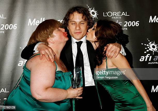 Comedian Magda Szubanski and singer Dannii Minogue kiss actor Heath Ledger who poses with his News Limited Reader's Choice Award in the Awards Room...
