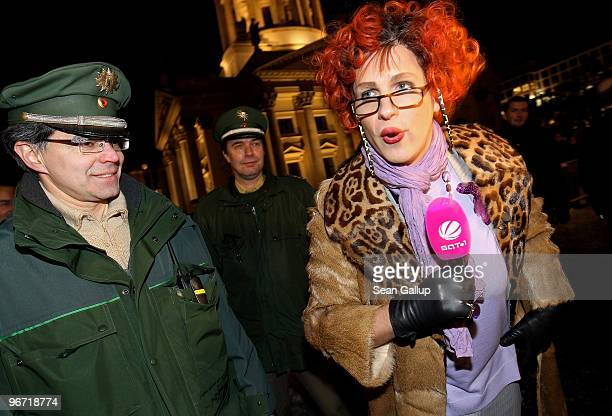 Comedian Oliver Pocher pretending to be a female society reporter for SAT1 television is escorted by police after attempting to get into the Cinema...