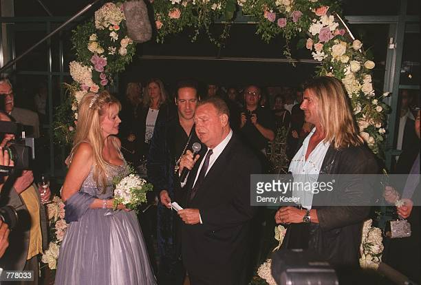 Comedian Rodney Dangerfield reads his vows to his wife Joan during their wedding ceremony August 28 2000 as Fabio right and Andrew Dice Clay center...