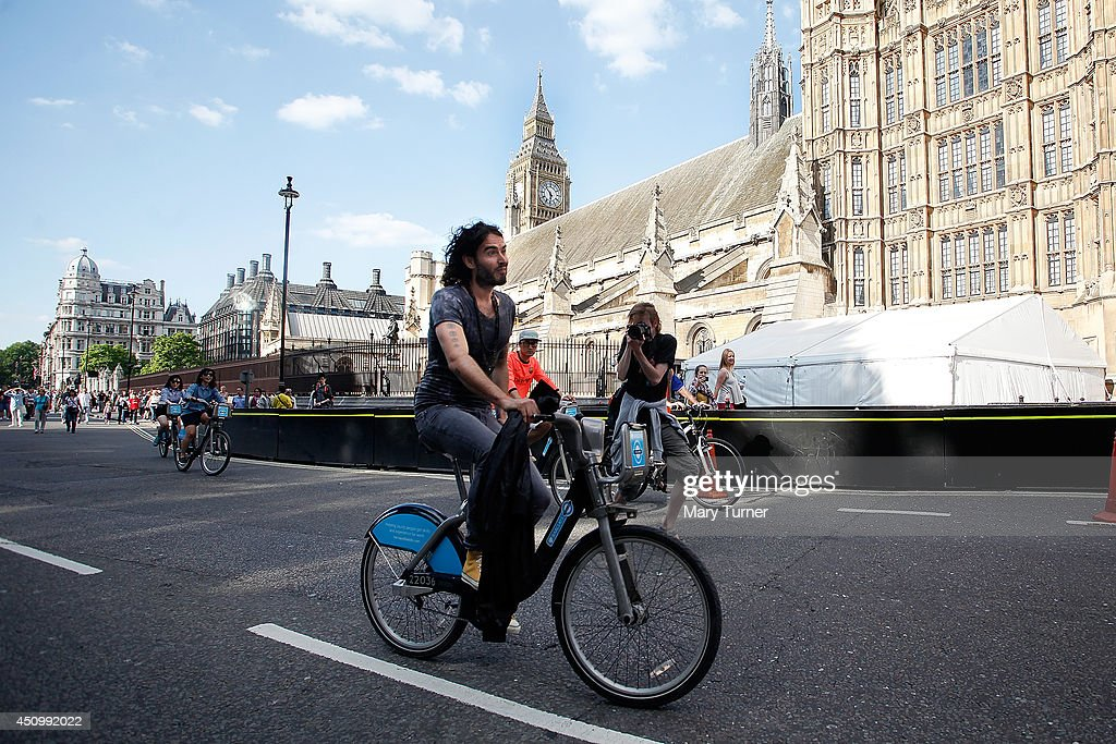 Comedian Russell Brand cycles away from Parliament Square on a hired 'Boris Bike' on June 21, 2014 in London, England. Russell Brand cycled away, past the Houses of Parliament, after speaking to a crowd of thousands that had gathered to protest against government austerity cuts.