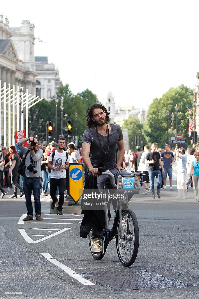 Comedian <a gi-track='captionPersonalityLinkClicked' href=/galleries/search?phrase=Russell+Brand&family=editorial&specificpeople=536593 ng-click='$event.stopPropagation()'>Russell Brand</a> cycles away from Parliament Square on a hired 'Boris Bike' on June 21, 2014 in London, England. <a gi-track='captionPersonalityLinkClicked' href=/galleries/search?phrase=Russell+Brand&family=editorial&specificpeople=536593 ng-click='$event.stopPropagation()'>Russell Brand</a> cycled away, past the Houses of Parliament, after speaking to a crowd of thousands that had gathered to protest against government austerity cuts.