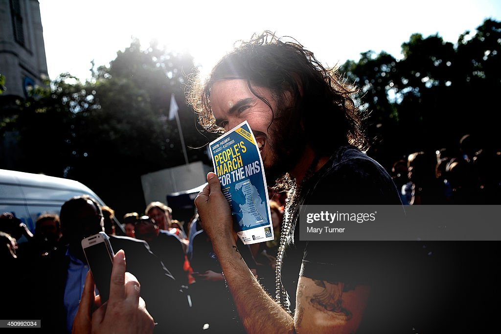 Comedian <a gi-track='captionPersonalityLinkClicked' href=/galleries/search?phrase=Russell+Brand&family=editorial&specificpeople=536593 ng-click='$event.stopPropagation()'>Russell Brand</a> holds a flyer for a pro-NHS demonstration as he speaks to a members of a crowd of thousands that gathered in Parliament Square to protest, on June 21, 2014 in London, England. The crowd marched from Oxford Circus to Parliament Square to voice their opposition to government austerity cuts.