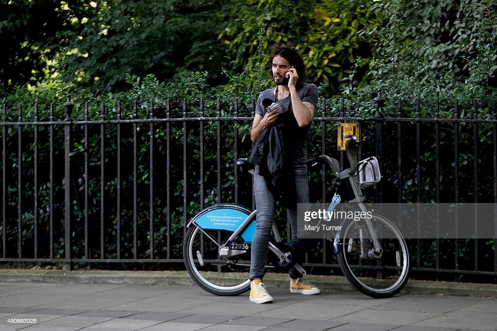 Comedian <a gi-track='captionPersonalityLinkClicked' href=/galleries/search?phrase=Russell+Brand&family=editorial&specificpeople=536593 ng-click='$event.stopPropagation()'>Russell Brand</a> speaks on his mobile phone, beside his hired 'Boris Bike' that he used to cycle away from a gathering at Parlaiment Square, on June 21, 2014 in London, England. <a gi-track='captionPersonalityLinkClicked' href=/galleries/search?phrase=Russell+Brand&family=editorial&specificpeople=536593 ng-click='$event.stopPropagation()'>Russell Brand</a> spoke to a crowd of thousands that had gathered to protest against government austerity cuts.