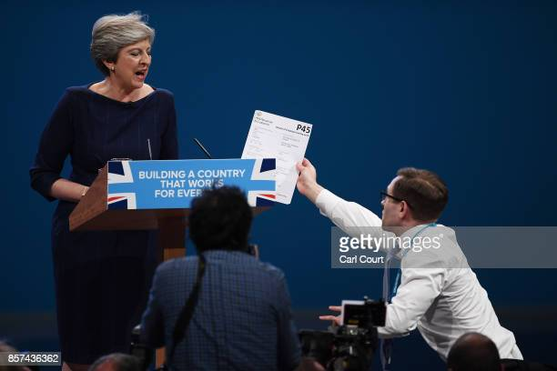 Comedian Simon Brodkin aka prankster Lee Nelson hands Prime Minister Theresa May a P45 during her keynote speech to delegates and party members on...