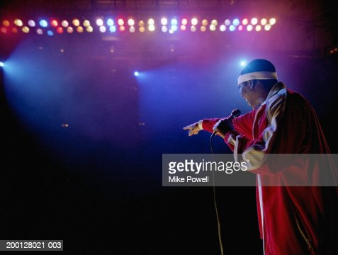 Comedian standing on stage pointing towards audience, rear view