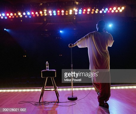 Comedian standing on stage, rear view