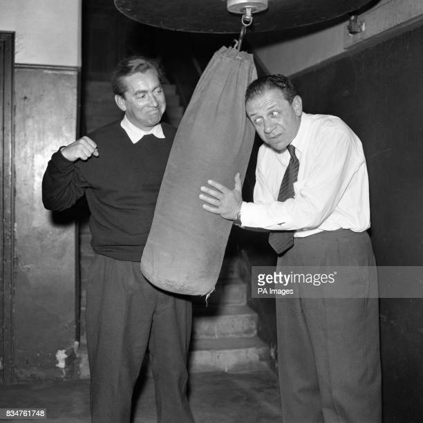 Comedian Tony Hancock limbers up with a punchbag assisted by a somewhat apprehensive Sidney James There's no fight ahead of Hancock who is just in...