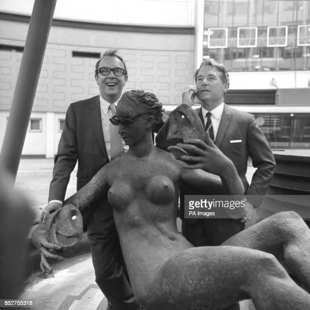 Comedians Eric Morecambe and Ernie Wise place sunglasses on a nude sculpture which is holding the masks of Comedy and Tragedy at the BBC Television...