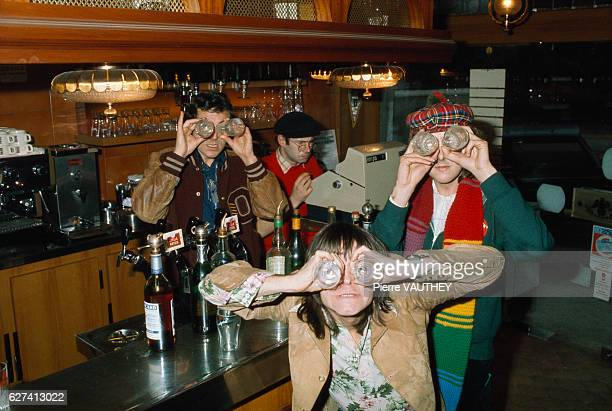 Comedians from the British comedy troupe Monty Python hold drinking glasses up to their eyes in a Paris bar In the background musician and supporting...