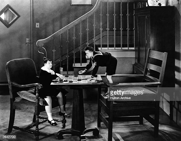 Comedians Stan Laurel and Oliver Hardy dressed in sailor suits and playing draughts on an oversized set as they appear in the film 'Brats' directed...