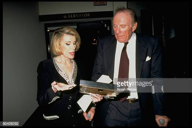 Comedian/TV talk show host Joan Rivers chatting w Orin Lehman while holding French painting 'A Park View' by unident artist that she has just bought...
