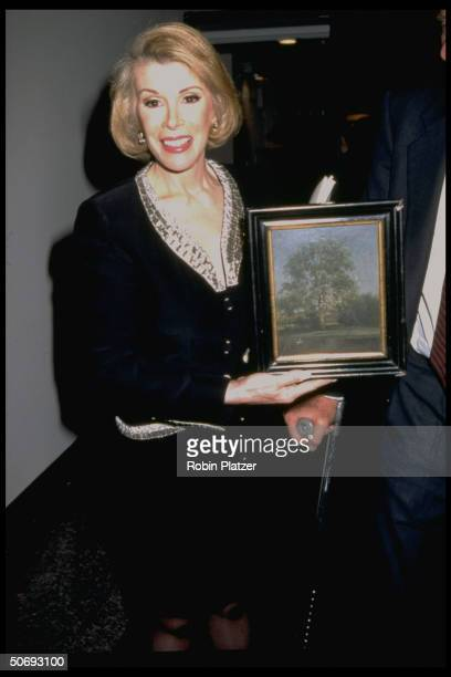 Comedian/TV talk show host Joan Rivers holding French painting 'A Park View' by unident artist that she bought at auction of estate of Jacqueline...