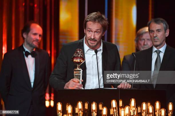 Comedie Francaise's general manager Eric Ruf holds the trophy after the play 'Les Damnes' won a Moliere award in the category 'theatre public' at the...