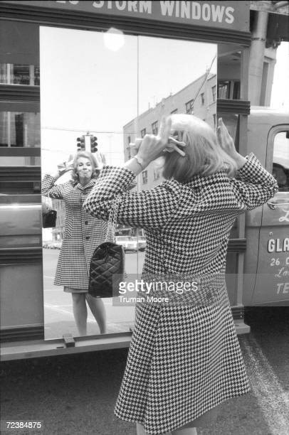 Comedienne Joan Rivers making faces in a mirror on the street [Scanned from contact sheet]