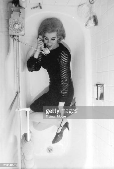 Comedienne Joan Rivers wearing black mesh dress and heels while talking on the phone in a bathtub [Scanned from contact sheet]