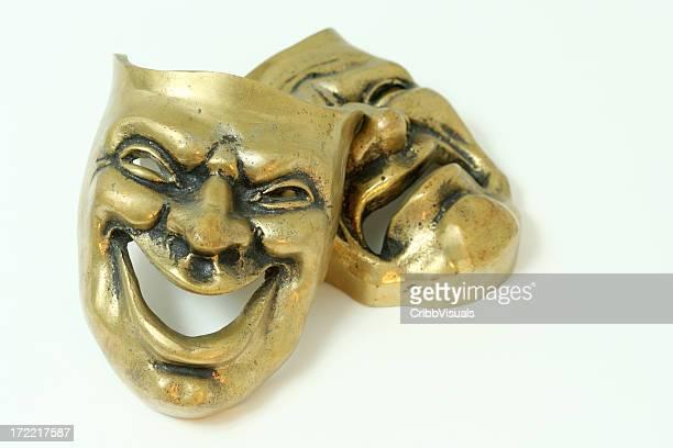 Máscaras comedia y tragedia de latón sobre fondo blanco