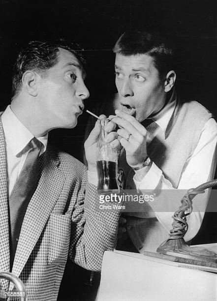 Comedy duo Dean Martin and Jerry Lewis quenching their thirst with a bottle of coke