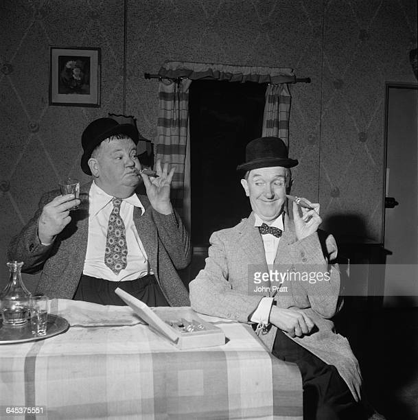 Comedy duo Stan Laurel and Oliver Hardy pause for a cigar in the sketch 'A Spot Of Trouble' performed on stage during their tour of the UK 25th...