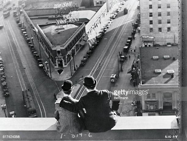 Comedy team Laurel and Hardy sitting atop building scaffolding look down on city street in film scene from the 1920s