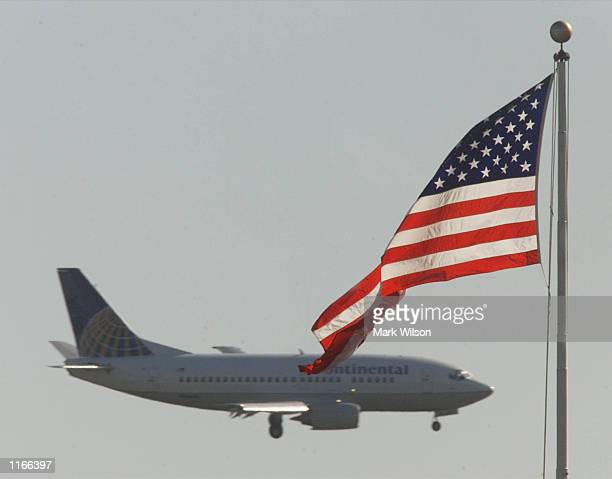 A comercial airliner flies past an American flag near the Pentagon during its approach to Reagan National Airport October 11 2001 in Arlington VA