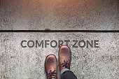 Comfort Zone Concept, Male with Leather Shoes Steps over a word : Comfort Zone with line on Concrete Floor, Top view